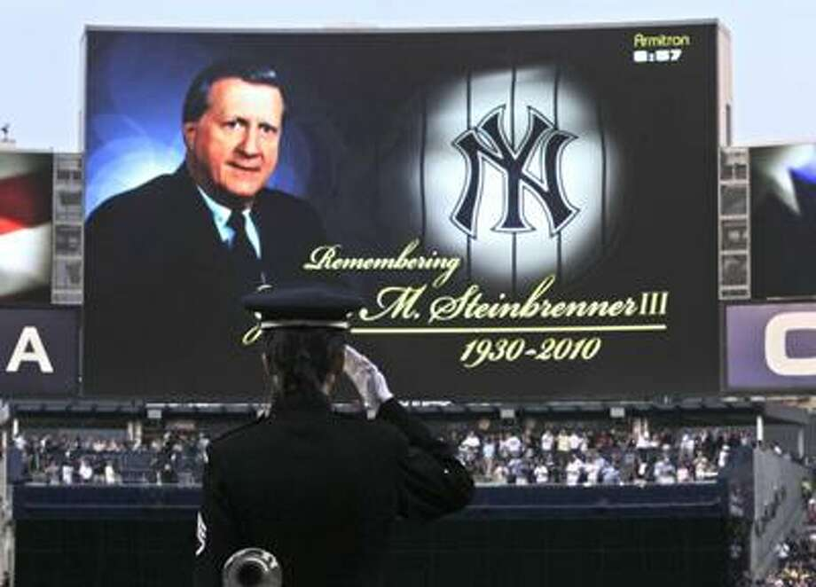 "Staff Sgt. Mikki Skinner, a bugler with the West Point Band, salutes after playing ""Taps"" during a tribute to New York Yankees owner George Steinbrenner, who died Tuesday, before a baseball game between the Tampa Bay Rays and the Yankees on Friday. (AP) Photo: ASSOCIATED PRESS / AP"