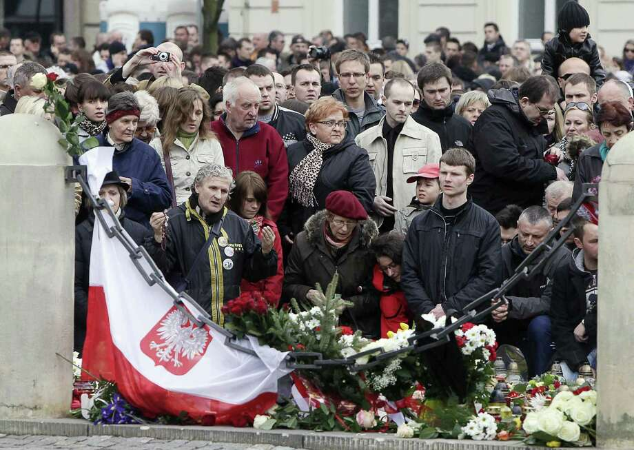 People mourn in front of the Presidential Palace in Warsaw, Poland, Saturday, April 10, 2010, after Polish President Lech Kaczynski died in a plane crash. Kaczynski, his wife and some of the country's highest military and civilian leaders died on Saturday when the presidential plane crashed as it came in for a landing in thick fog in western Russia, killing 96. (AP Photo/Czarek Sokolowski) Photo: ASSOCIATED PRESS / AP2010