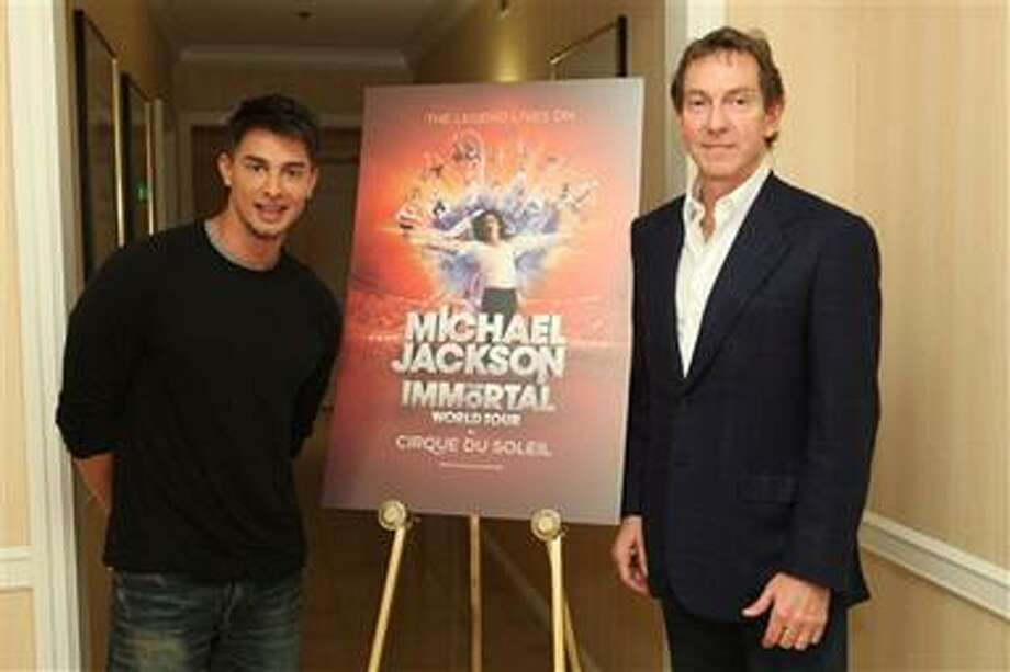"In this publicity image released by Cirque du Soleil, Jamie King, writer and director of  ""Michael Jackson The Immortal World Tour"" by Cirque du Soleil, left, and John Branca, co-executor of the Michael Jackson estate, stand by a promotional poster, Wednesday, Nov. 3, 2010 in Los Angeles where the Estate of Michael Jackson and Cirque du Soleil announced the launch of the production combining Michael Jackson music and choreography with Cirque du Soleil performers. The tour begins in October 2011 in Montreal. (AP Photo/Cirque du Soleil, Jake Novak) Photo: AP / Jake Novak©Berliner Photography/BEImages"