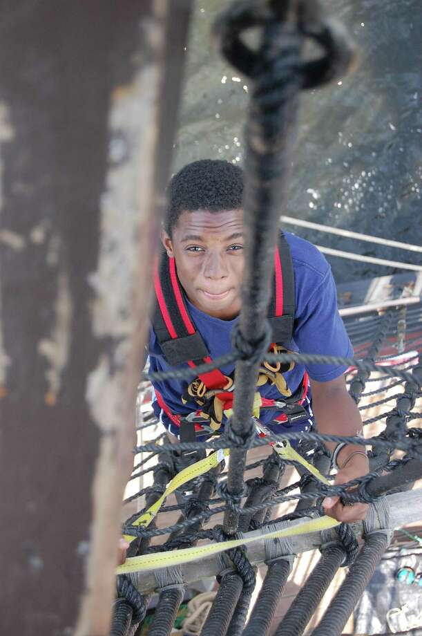 Raheem Reid, 15, a rising sophomore at the Connecticut River Academy in East Hartford, climbs down the rigging of the 'Half Moon,' a replica of Henry Hudson's ship, as it approaches Middletown on Monday.