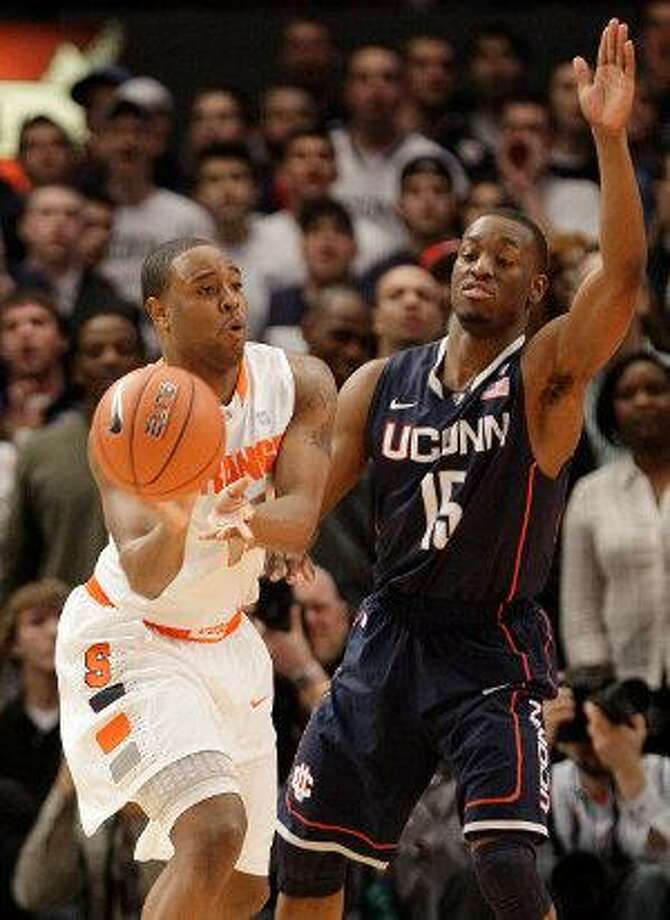 AP  Syracuse's Scoop Jardine (11) passes away from Connecticut's Kemba Walker (15) during the first half of a Big East Championship semifinal Friday night in New York.