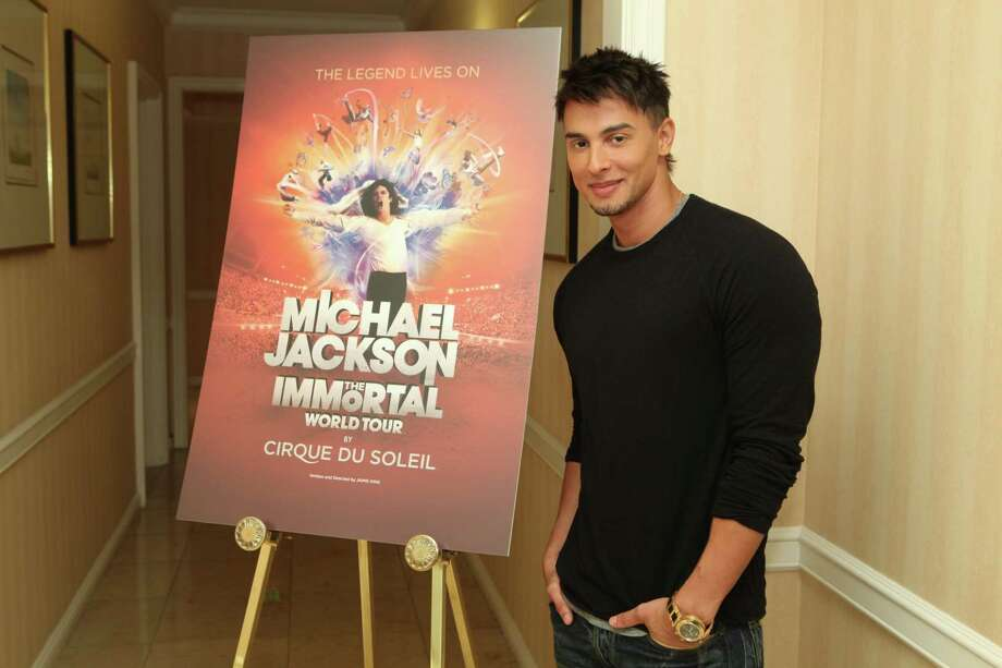 """In this publicity image released by Cirque du Soleil, Jamie King, writer and director of  """"Michael Jackson The Immortal World Tour"""" by Cirque du Soleil, stands by a promotional poster, Wednesday, Nov. 3, 2010 in Los Angeles where the Estate of Michael Jackson and Cirque du Soleil announced the launch of the production combining Michael Jackson music and choreography with Cirque du Soleil performers. The tour begins in October 2011 in Montreal. (AP Photo/Cirque du Soleil, Jake Novak) Photo: ASSOCIATED PRESS / Cirque du Soleil"""