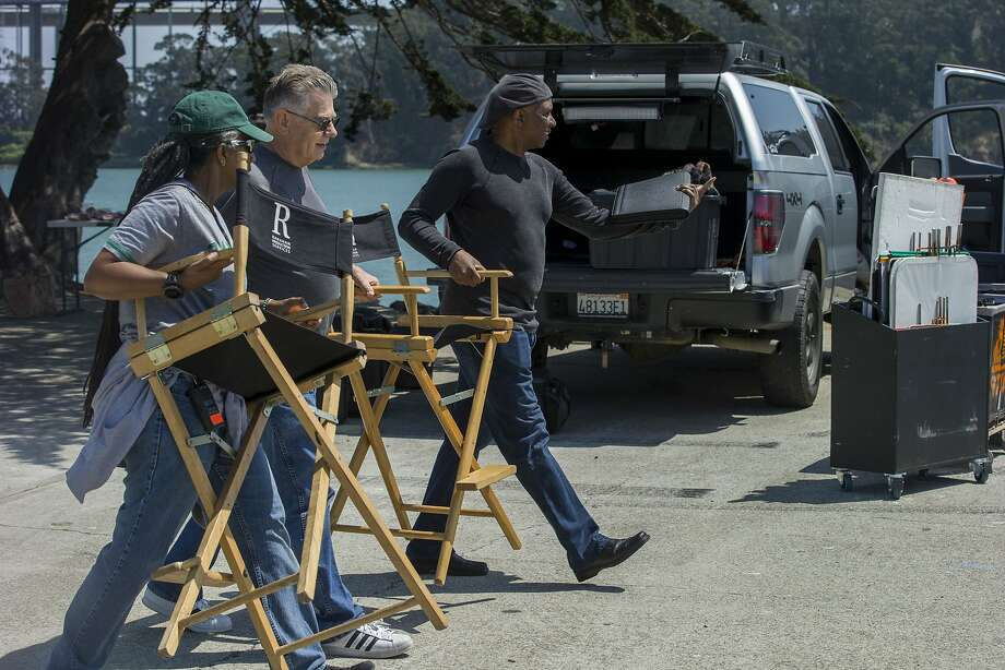 """Kim Bass (right) gets help bringing his chair to the set on Treasure Island to film some shots for """"Headshop."""" Photo: Santiago Mejia, The Chronicle"""