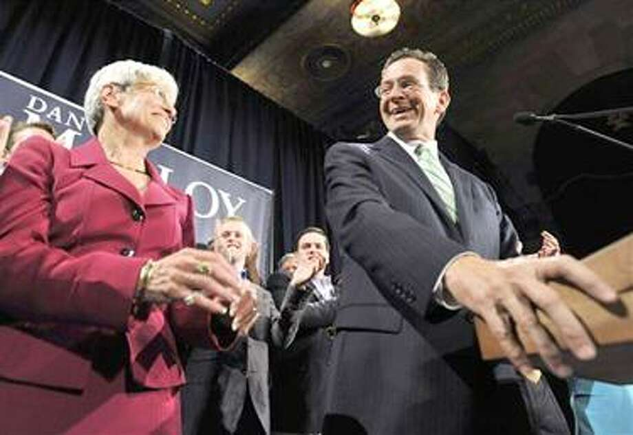 Democratic candidate for governor Dan Malloy, right, looks at running mate Nancy Wyman while addressing supporters in Hartford, Conn., early Wednesday, Nov. 3, 2010.  (AP Photo/Jessica Hill) Photo: AP / AP2010
