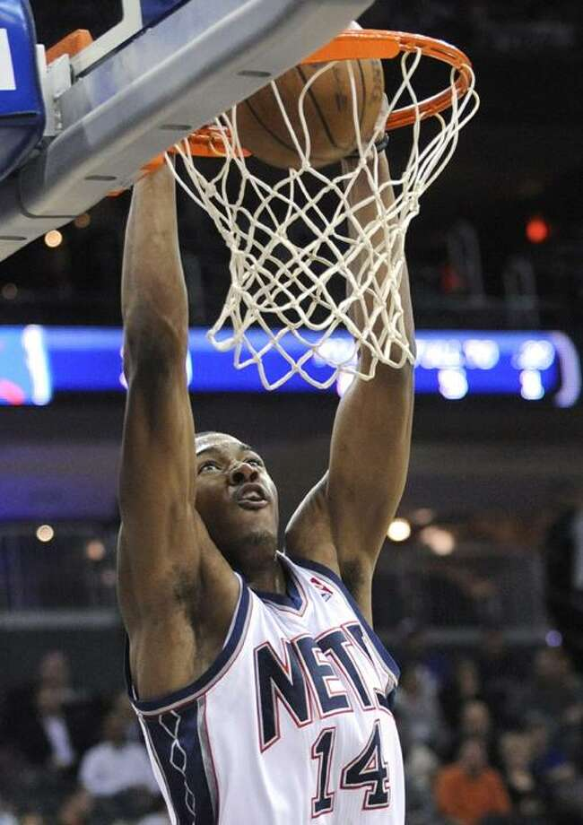 New Jersey Nets' Derrick Favors dunks the ball during the second quarter of an NBA basketball game against the Charlotte Bobcats, Wednesday in Newark, N.J. (AP Photo/Bill Kostroun) Photo: AP / FR51951 AP
