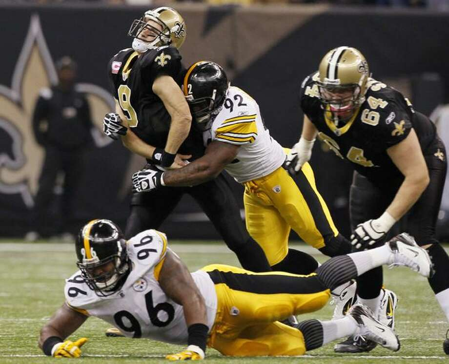 New Orleans Saints quarterback Drew Brees (9) is hit by Pittsburgh Steelers linebacker James Harrison (92) after releasing a pass during the first half of an NFL football game at the Louisiana Superdome in New Orleans, Sunday. Also in on the play are Steelers defensive end Ziggy Hood (96) and Saints offensive tackle Zach Strief (64). (AP Photo/Patrick Semansky) Photo: AP / ap