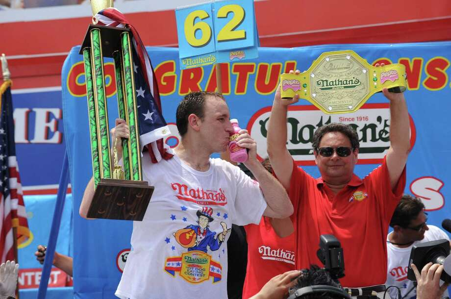 Champion Joey Chestnut kisses a bottle of Pepto-Bismol after eating 62 hot dogs at the Nathan's Famous Fourth of July International Hot Dog Eating Contest, Monday, July 4, 2011, in Coney Island, NY.   Pepto-Bismol is the official stomach remedy of the contest. (Diane Bondareff/AP Images for Pepto-Bismol) Photo: AP Images / AP2011