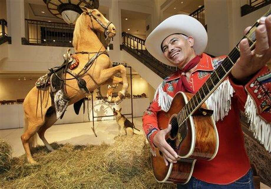"FILE - In this file photo of Friday July 9, 2010 the preserved remains of Roy Rogers' horse ""Trigger"" and dog ""Bullet"" are on display as Gil Perez, right, a doorman at Christies auction house, wears an outfit and holds a guitar belonging  to Rogers, at the auction house in New York.  A Nebraska cable TV network ponied up $266,500 for Roy Rogers' stuffed and mounted horse, Trigger, at an auction at Christie's in New York City on Wednesday July 14.  (AP Photo/Richard Drew, File) Photo: AP / AP"