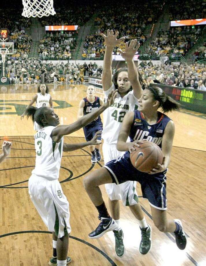 Baylor guard Jordan Madden (3) and Brittney Griner (42) combine to stop a drive to the basket by Connecticut guard Bria Hartley, front, in the first half of an NCAA college basketball game Sunday, Dec. 18, 2011, in Waco, Texas. (AP Photo/Tony Gutierrez) Photo: AP / AP