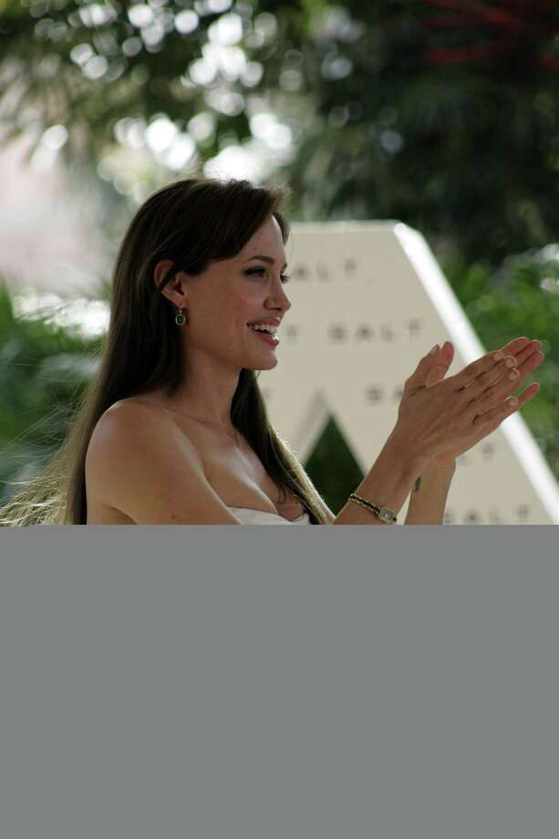American actress Angelina Jolie gestures while posing for photographers during a media event to promote her new movie Salt, in Cancun, Mexico, Wednesday June 30, 2010. In the movie Jolie plays the role of Evelyn Salt, a CIA officer accused of being a Russian spy. (AP Photo/Israel Leal) Photo: ASSOCIATED PRESS / AP