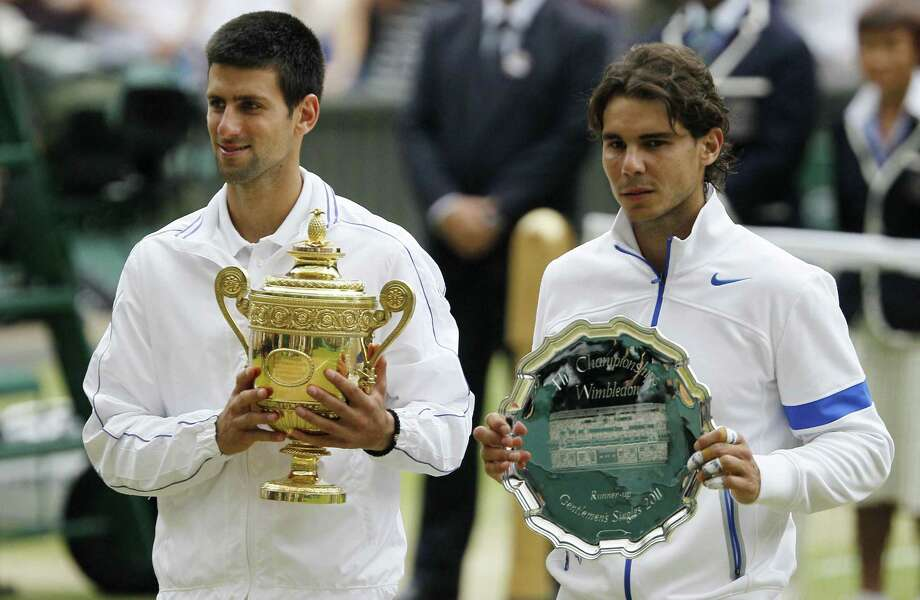 Serbia's Novak Djokovic and Spain's Rafael Nadal, right, hold their trophies after Novak Djokovic defeated Rafael Nadal in the men's singles final at the All England Lawn Tennis Championships at Wimbledon, Sunday, July 3, 2011. (AP Photo/Alastair Grant) Photo: ASSOCIATED PRESS / AP2011