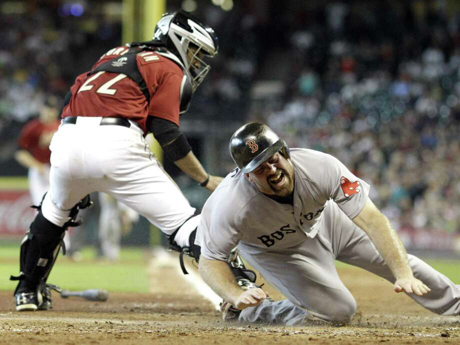 Boston Red Sox's Kevin Youkilis, right, reacts as Houston Astros catcher Carlos Corporan (22) lands on him after leaping to catch the throw at home plate during the fourth inning of an interleague baseball game Sunday, July 3, 2011, in Houston. Youkilis was safe on the play. (AP Photo/David J. Phillip) Photo: ASSOCIATED PRESS / AP2011