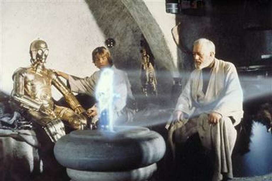 """In this publicity image released by LucasFilm Ltd & TM, characters, from left, Anthony Daniels  portraying C-3PO, Mark Hamill portraying Luke Skywalker and Alec Guinness portraying Ben Obi-Wan Kenobi look at a hologram of Princess Leia, portrayed by Carrie Fisher in a scene from the original 1977 """"Star Wars"""" film. (AP Photo/Lucasfilm Ltd & TM) Photo: AP / © Lucasfilm Ltd & TM"""