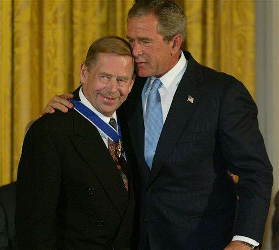 FILE - President Bush embraces Vaclav Havel, former president of the Czech Republic, after presenting him with the Presidential Medal of Freedom in the East Room of the White House in this July 23, 2003 file photo. The Presidential Medal of Freedom is the highest civilian award of the U.S. government. Havel, the dissident playwright who wove theater into politics to peacefully bring down communism in Czechoslovakia and become a hero of the epic struggle that ended the Cold War, died Sunday Dec. 18, 2011 in Prague. He was 75.  (AP Photo/Charles Dharapak, File) Photo: AP / AP2003