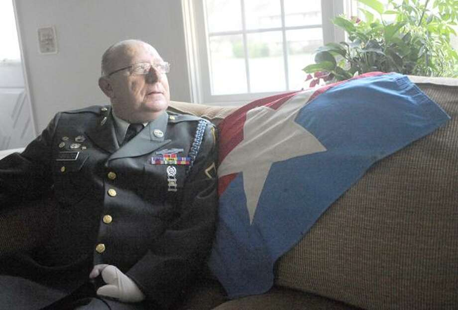 ADVANCE FOR WEEKEND EDITIONS DEC. 17-18 - This Nov. 30, 2011 photograph shows Harold Farrington, Jr., in his Old Saybrook, Conn. home.  Farrington is a member of the Class of 2011 that was inducted into the Connecticut Veterans Hall of Fame. Both of Farrington's hands, one of which is shown in the bottom of the portrait, were injured during the Vietnam War.(AP Photo/Abigail Pheiffer,The Day) Photo: AP / Copyright 2011- The Day Publishing Company
