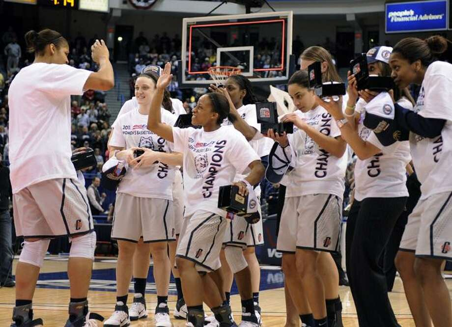 AP Connecticut players celebrate and look at tournament gifts after defeating Notre Dame 73-64 in an NCAA college basketball game for the Big East tournament championship in Hartford, on Tuesday.