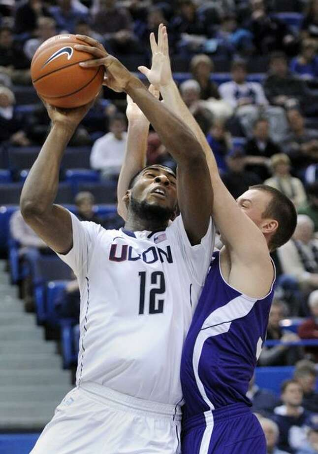 Connecticut's Andre Drummond (12) is fouled by Holy Cross' Jordan Stevens during the second half of an NCAA college basketball game in Hartford, Conn., on Sunday, Dec. 18, 2011. Drummond scored a game-high 24 points in his team's 77-40 victory. (AP Photo/Fred Beckham) Photo: AP / AP2011
