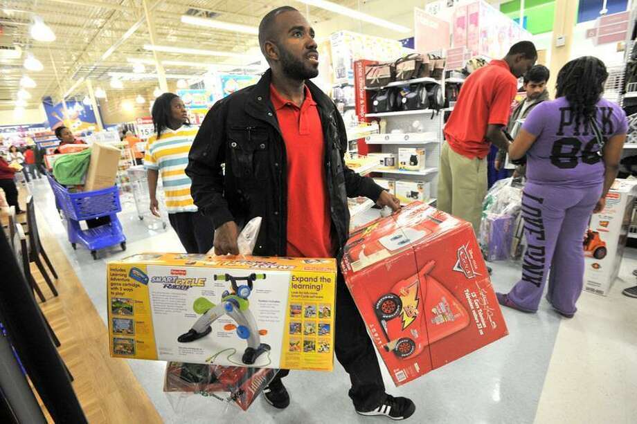 John Rosser of Atlanta rushes to the start line for check out at the Toys R Us store in Atlanta Nov. 24. People who rushed to snag discounts on TVs, toys and other gifts are quickly returning them for much-needed cash. (Associated Press) Photo: AP / © 2011 Atlanta Journal Constitution