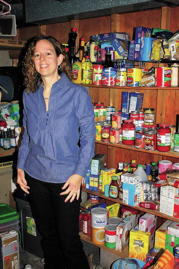 In this Feb. 17, photo, Gina Juliano stands beside some items she received at a sharp discount at her Enfield, Conn., home. Juliano spent just $2,200 in 2010 and got $11,000 worth of merchandise through coupon clipping and smart shopping. (AP Photo/Journal Inquirer, Julie Sprengelmeyer) Photo: AP / Journal Inquirer