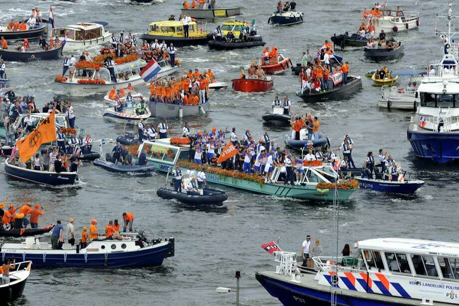 The Netherlands' World Cup soccer team travels on a green boat, center, prior to a boat tour through Amsterdam's canals, Netherlands, Tuesday, during a day of celebrations as World Cup tournament runner-up. (AP Photo/Evert Elzinga) Photo: ASSOCIATED PRESS / AP