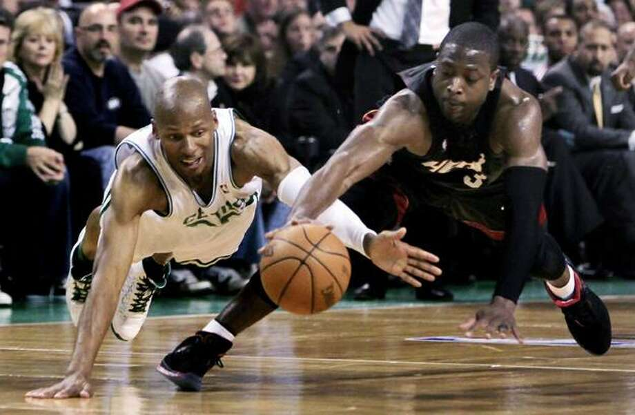 This April 27, 2010, file photo shows Boston Celtics guard Ray Allen, left, and Miami Heat guard Dwyane Wade diving for a loose ball during the first half of a first-round NBA basketball playoff game in Boston. Allen said on Tuesday that he didn't want to uproot his family and make them adjust to a new city. His first choice was to stay in Boston, and things worked out for a two-year deal worth about $20 million. (AP Photo/Charles Krupa) Photo: AP / AP2010