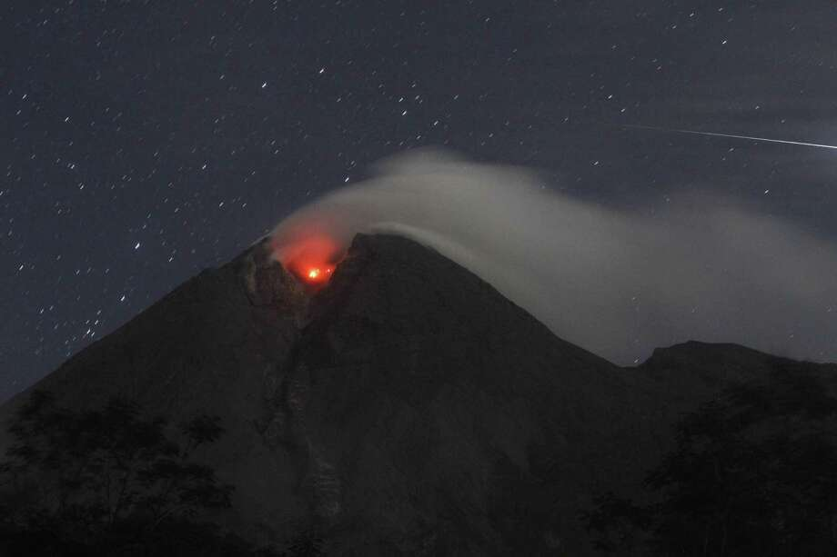 Mount Merapi spews volcanic smoke as seen from Deles, Indonesia, early Monday, Nov. 1, 2010. Indonesia's most volatile volcano unleashed its most powerful eruption in a deadly week Monday, spewing searing clouds of gas and debris thousands of feet (meters) into the air. There were no immediate reports of new casualties. (AP Photo/Irwin Fedriansyah) Photo: AP / AP