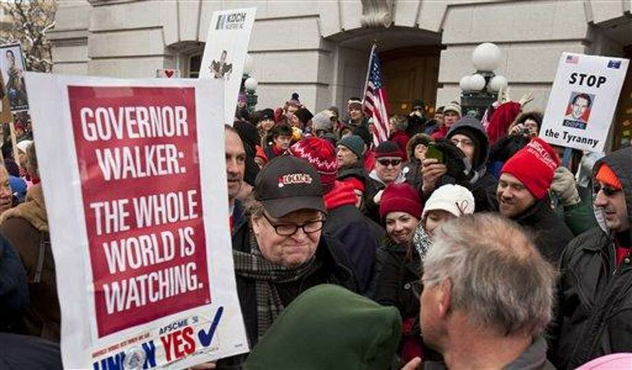Filmmaker Michael Moore, center, makes his way through a crowd at the state Capitol in Madison, Wis., Saturday, March 5, 2011, on the 18th day of protests over the governor's proposed budget that would eliminate collective bargaining rights for many state workers. (AP Photo/Andy Manis) Photo: AP / FR19153 AP
