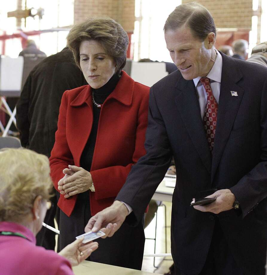 Connecticut Attorney General and Democratic candidate for the Senate Richard Blumenthal, right, presents his identification to a poll worker as he and his wife Cynthia, in red, prepare to vote at the Bendheim Western Greenwich Civic Center in Greenwich, Conn., Tuesday, Nov. 2, 2010. (AP Photo/Stephan Savoia) Photo: ASSOCIATED PRESS / AP