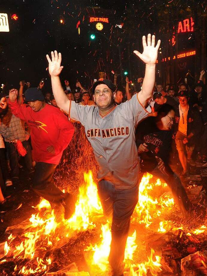 Giants fan Ron Galileo jumps through a bonfire outside AT&T Park Monday in San Francisco after the Giants won the World Seriesd. (AP Photo/Noah Berger) Photo: AP / FR34727 AP