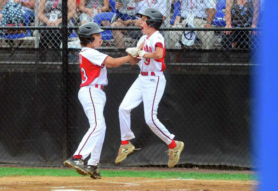Sean O'Neil and Ethan Righter, left, celebrate scoring two runs during Little League New England Regional. Photo: Christian Abraham / Hearst Connecticut Media / Connecticut Post