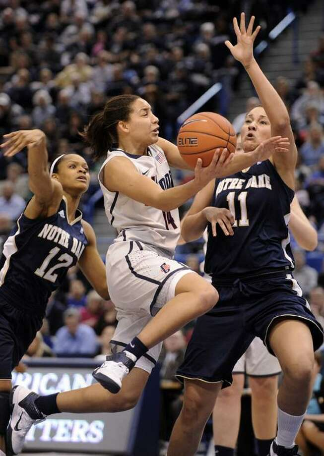 Connecticut's Bria Hartley, center, drives past Notre Dame's Frederica Miller, left, and Natalie Achonwa during the first half an NCAA college basketball game in the final of the Big East tournament in Hartford, Conn., on Tuesday, March 8, 2011. (AP Photo/Fred Beckham)