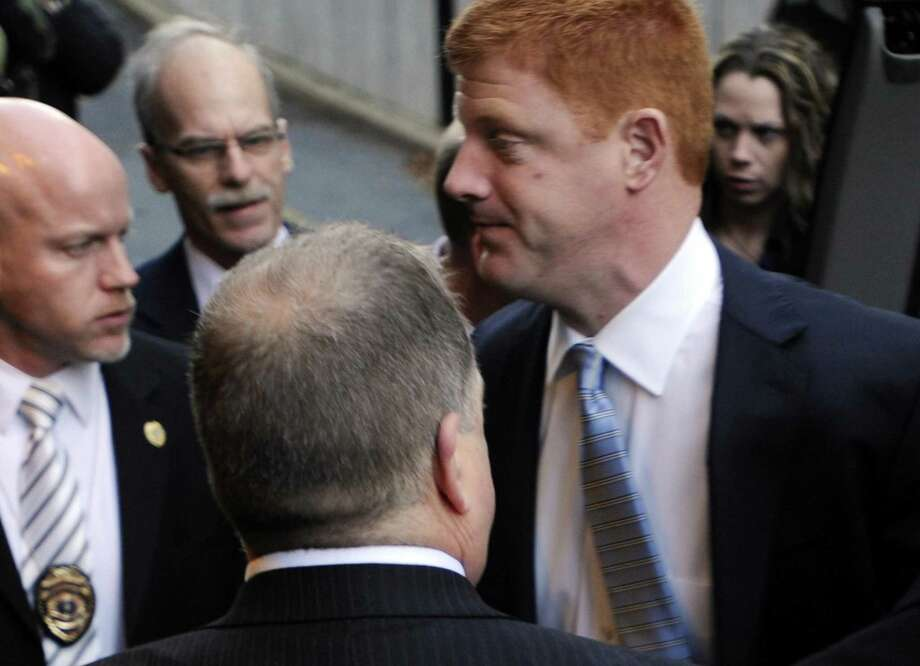 Penn State assistant football coach Mike McQueary, right, arrives at Dauphin County Court surrounded by heavy security Friday in Harrisburg, Pa. McQueary declined to speak to reporters Friday as he entered the courthouse in Harrisburg for the hearing for Gary Schultz and Tim Curley, who are set to appear for a preliminary hearing related to the Jerry Sandusky child sex abuse case. (AP Photo/Bradley C Bower) Photo: ASSOCIATED PRESS / AP2011
