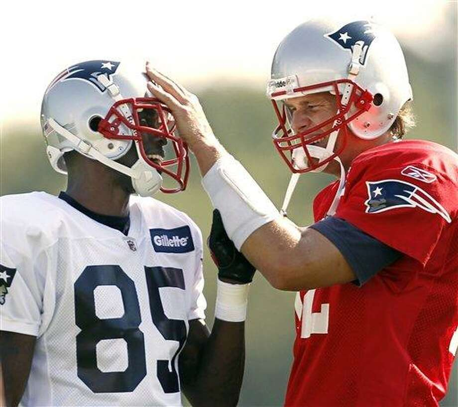 FILE - In this July 30, 2011 file photo, New England Patriots quarterback Tom Brady, right, fools around with new teammate Chad Ochocinco during NFL football training camp in Foxborough, Mass. Ochocinco goes into his final exhibition game with the Patriots on Thursday night with just two catches. But he says his work in practice is more important as he gets up to speed with Brady and a new offense. (AP Photo/Winslow Townson, File) Photo: AP / AP2011