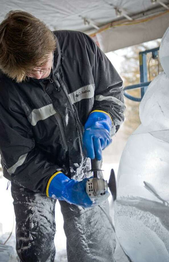 """Bill Covitz, internationally renowned ice carver, former national champion, and owner of Ice Matters in Waterbury, puts the finishing touches on his winning """"Ice Wars"""" sculpture, at Lyman Orchards' 39th Annual Winterfest."""