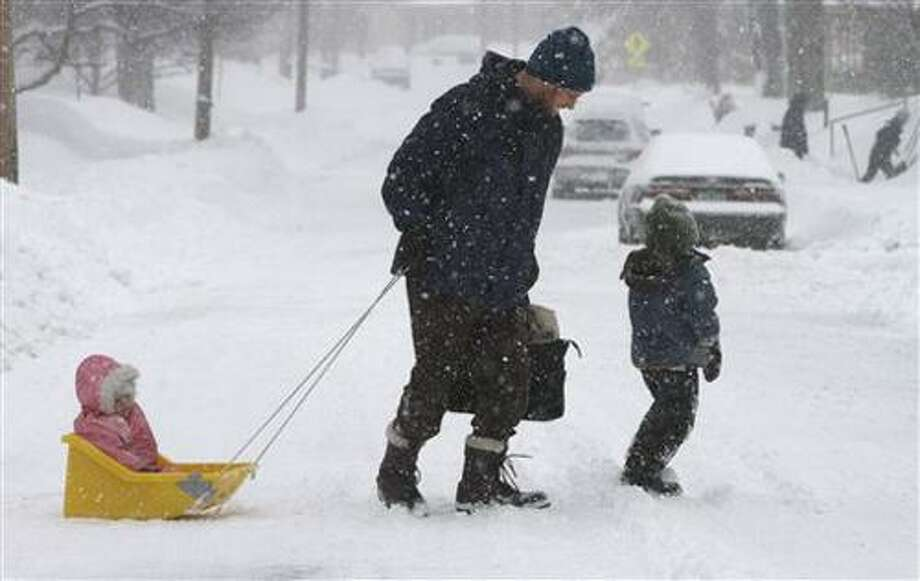 Donald Devoil, center, takes his children to a neighbor's house since his daycare was closed due to a winter storm on Monday, March 7, 2011 in Montpelier, Vt.  Meteorologist Bruce Taber says 20.6 inches of snow has fallen at the Burlington International Airport and it's supposed to keep snowing through the early afternoon. He says some parts of northern Vermont could get up to 30 inches of snow. At left is Isla, 1, and at right is Callum, 5. (AP Photo/Toby Talbot) Photo: AP / AP