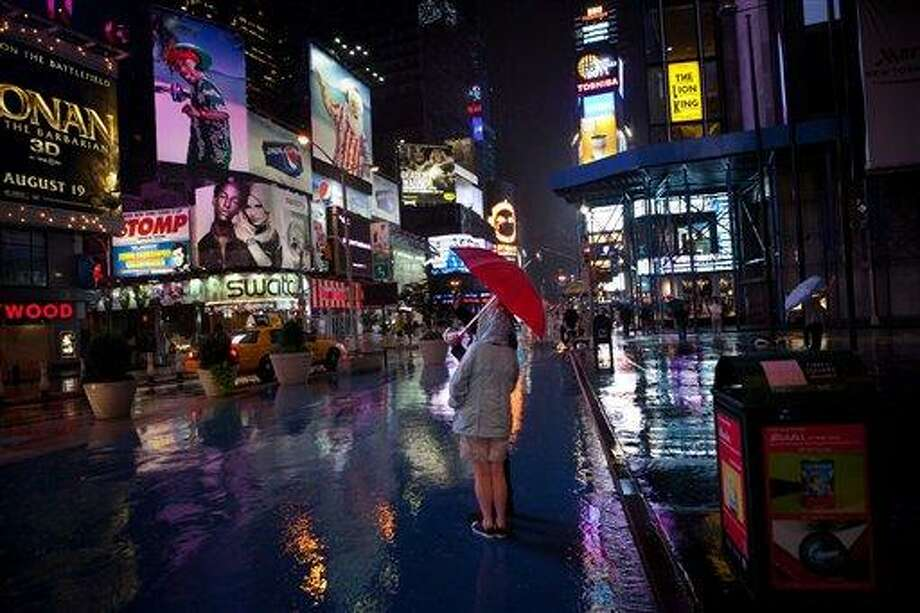 The looming threat of Hurricane Irene did not dissuade tourists from visiting Manhattan's Times Square, Saturday, Aug. 27, 2011, in New York. Mayor Bloomberg advised all New Yorkers to prepare as the region girded for wind, rain, and flooding as the storm stood poised to bear down on an already saturated New York state. (AP Photo/John Minchillo) Photo: ASSOCIATED PRESS / AP2011