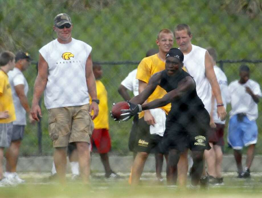 Minnesota Viking quarterback Brett Favre watches as an Oak Grove High School football player hauls in a pass during a voluntary summer practice in Hattiesburg, Miss., Monday. Favre has been a fixture at the school for several summers, taking his turn at quarterback and passing to the high school players during their voluntary summer practices. (AP Photo/Rogelio V. Solis) Photo: AP / AP