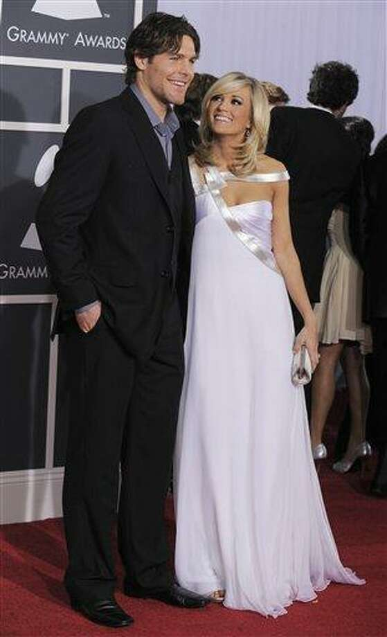 "Carrie Underwood and Mike Fisher arrives at the Grammy Awards in this Jan. 31 file photo taken in Los Angeles. Grammy-winning country singer Underwood has married Ottawa Senators hockey player Mike Fisher at a resort in Georgia Saturday. ""Yes, Mike and Carrie are married,"" Underwood's publicist Jessie Schmidt said in an e-mail to The Associated Press early Sunday. (AP) Photo: AP / AP2010"