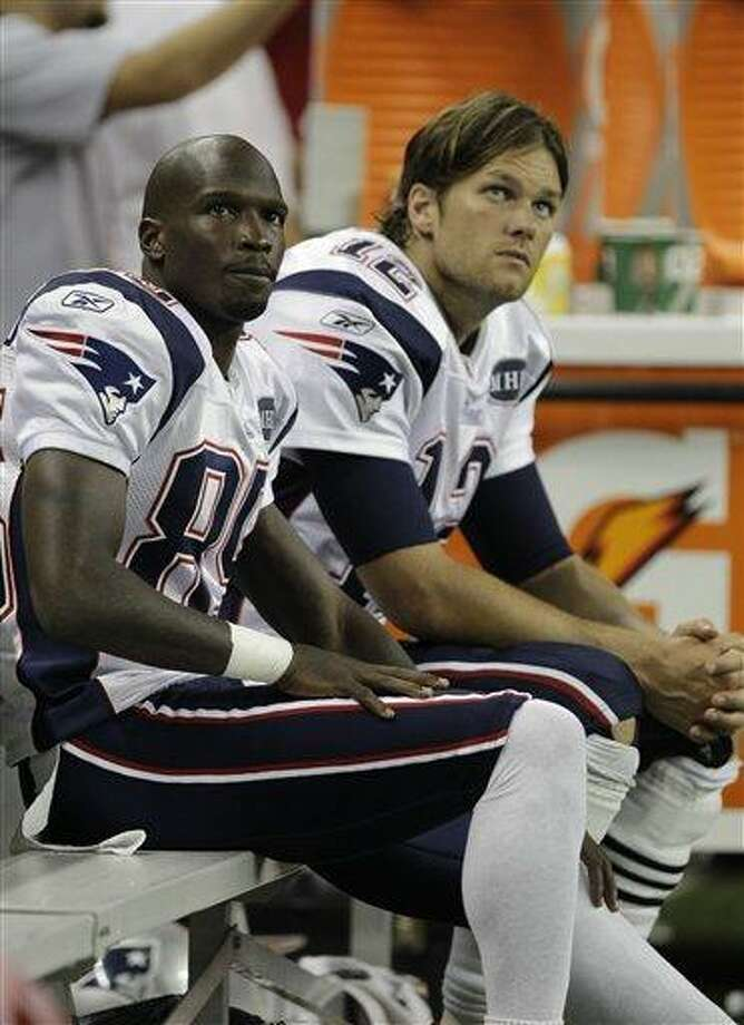 New England Patriots wide receiver Chad Ochocinco, left, and quarterback Tom Brady watch during of an NFL preseason football game against the Detroit Lions in Detroit, Saturday, Aug. 27, 2011. (AP Photo/Paul Sancya) Photo: AP / 2011 AP