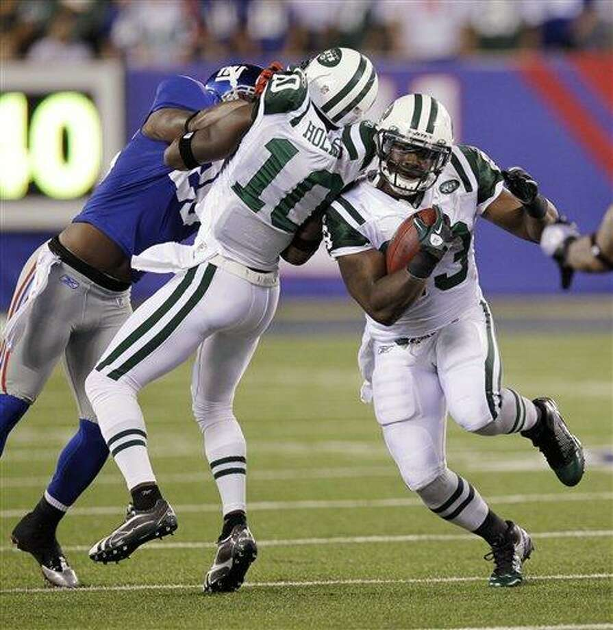 New York Jets' Shonn Greene runs the ball while teammate Santonio Holmes, center, blocks New York Giants' Antrel Rolle during the second quarter of an NFL preseason football game Monday, Aug. 29, 2011, in East Rutherford, N.J. (AP Photo/Julio Cortez) Photo: AP / AP