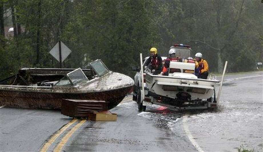 The Arr-Mac water rescue team from Wayne County maneuvers around a beached boat in the middle of Hwy. 304 Saturday, Aug. 27, 2011 in Mesic, N.C. Hurricane Irene knocked out power and piers in North Carolina, clobbered Virginia with wind and churned up the coast Saturday to confront cities more accustomed to snowstorms than tropical storms. New York City emptied its streets and subways and waited with an eerie quiet. (AP Photo/The News & Observer, Chris Seward) Photo: AP / 2011 The News and Observer