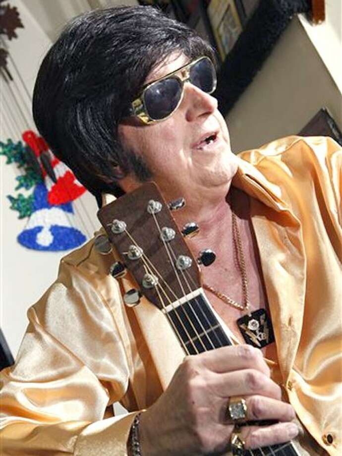 Ted Prior, 67, dressed as Elvis Presley, holds a guitar as he sits in his home Wednesday, Dec. 29, 2010, in Galloway Township, N.J. This New Year's Eve, for the first time he can remember, Prior won't be gyrating on a stage somewhere, warning someone not to step on his blue suede shoes. Cancer that has spread throughout his body is forcing Prior to miss a scheduled concert in Ocean City -- it's the first time in a 50-year career spanning nearly 10,000 performances that south Jersey's answer to The King has had to miss a show. (AP Photo/Mel Evans) Photo: AP / AP