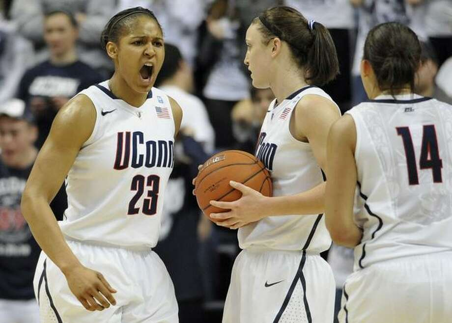 Connecticut's Maya Moore, left, reacts to a foul against Connecticut as teamamtes Kelly Faris, center, and Bria Hartley (14) look on, during the second half of an NCAA college basketball game against Notre Dame, in Storrs, Conn., Saturday, Feb. 19, 2011. (AP Photo/Jessica Hill) Photo: ASSOCIATED PRESS / AP2011