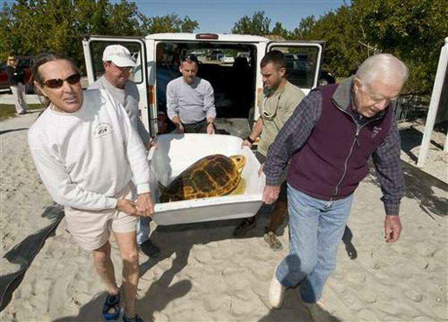 """In this photo released by the Florida Keys News Bureau, former President Jimmy Carter, right, helps carry """"Danger,"""" a loggerhead sea turtle to be released off the Florida Keys, in Marathon, Fla., Tuesday, Dec. 28, 2010. At left is Richie Moretti, founder of The Turtle Hospital that rehabilitated the reptile after it was discovered ill. Carter and his family toured the hospital and participated in the release as a facet of their vacation in the Florida Keys. (AP Photo/Florida Keys News Bureau, Andy Newman) NO SALES Photo: AP / Florida Keys News Bureau"""