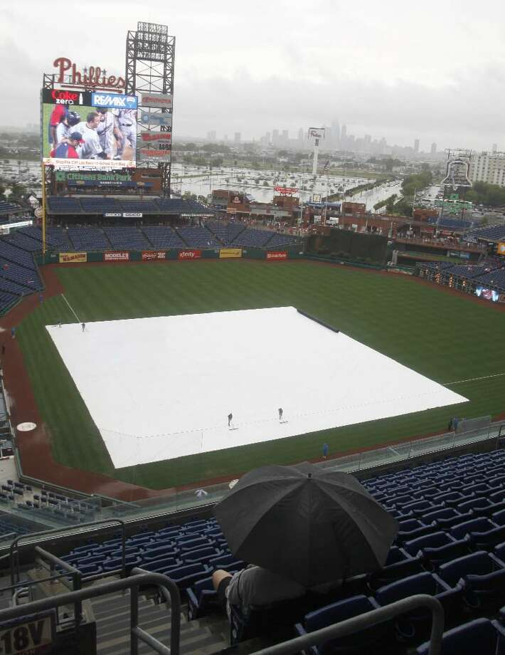 ASSOCIATED PRESS A fan huddles under an umbrealla as the infield is covered in a tarp as rain falls before the start of a baseball game between the Florida Marlins and the Philadelphia Phillies Saturday in Philadelphia. The doubleheader was postponed because of Hurricane Irene.