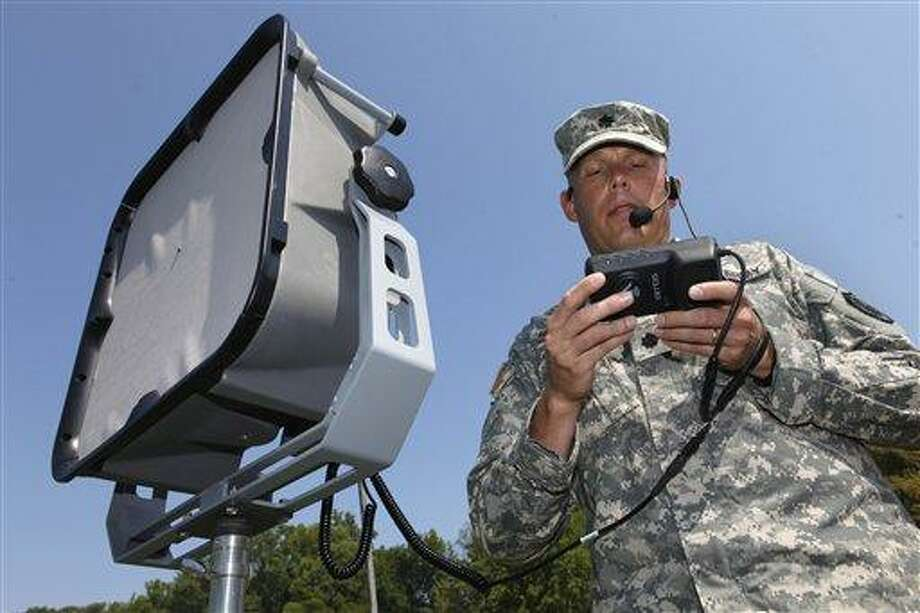 In this photo taken Sept. 14, 2011, Lt. Col. Jeffrey Bevington, requirements officer with the Joint Non-Lethal Weapons Directorate, demonstrates one of the military's latest voice projection systems and instant translation technologies, which can project a human voice a mile away and instantly translate from English to another language, at the Marine Base in Quantico Va. Associated Press Photo: AP / AP