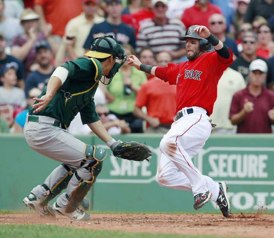ASSOCIATED PRESS Boston Red Sox second baseman Dustin Pedroia, right, scores past Oakland Athletics catcher Kurt Suzuki on an RBI triple by the David Ortiz during the third inning of Saturday's game in Boston.