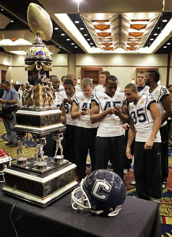 Connecticut players look at the images they took of the Fiesta Bowl trophy during the Fiesta Bowl media day Wednesday, Dec. 29, 2010, in Scottsdale, Ariz. Connecticut is scheduled to face Oklahoma in the Fiesta Bowl NCAA college football game, on Jan. 1, 2011. (AP Photo/Matt York) Photo: AP / AP