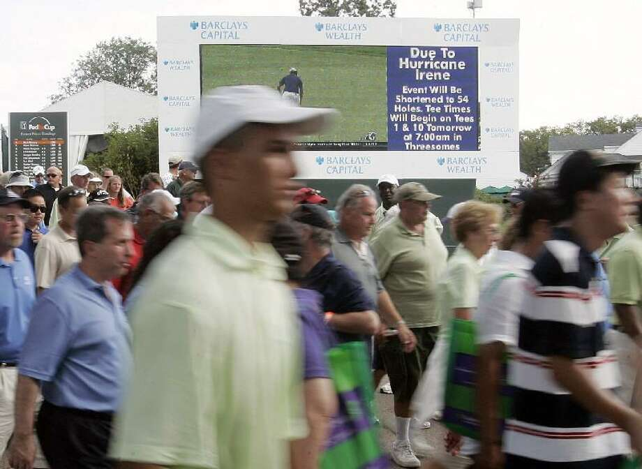 ASSOCIATED PRESS Spectators pass by a video board during the second round of The Barclays golf tournament Friday in Edison, N.J. The fans were alerted that due to Hurricane Irene, tournament will be shortened to a 54-hole tournament ending Saturday, and not Sunday.