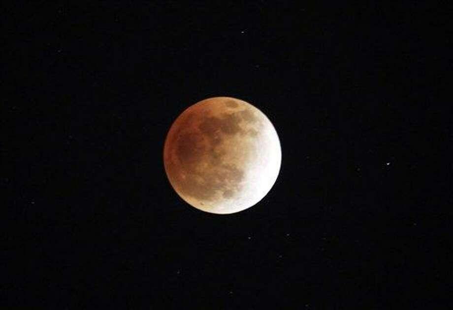 Lunar eclipse is seen in Shanghai, China, on Saturday, Dec. 10, 2011.  (AP Photo/Eugene Hoshiko) Photo: AP / AP